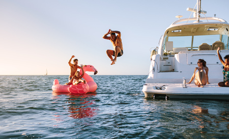 Man diving in the sea with friends sitting on yacht and inflatable toy. Group of friends enjoying a summer day on a inflatable toy and yacht.