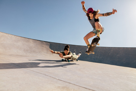 Two women doing stunts on skateboards at skate park. Female friends practising skateboarding outdoors. Фото со стока