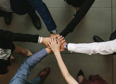 Overhead view of business people hands stacked together. Business team showing unity.