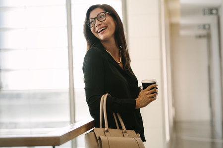 Smiling business woman standing in office with cup of coffee . Female executive standing in office during break.