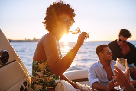 African woman drinking during sunset boat party with friends. Group of men and women having a boat party during sunset.