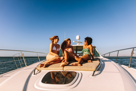 Three girls sitting on the deck of a private yacht in the sea. Smiling female friends in swimsuits relaxing on yacht deck and chatting.