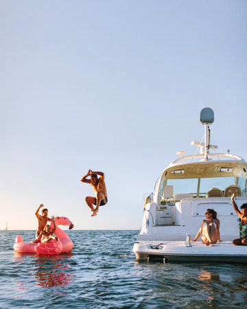 Young man jumping off the boat in to the sea. Young people having fun during party on a private boat. Men and women on yacht and inflatable toy in sea. Banque d'images