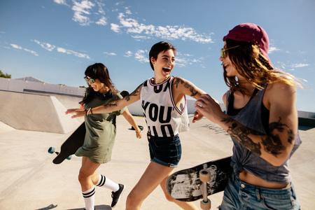 Group of female skaters running and having fun at skate park. Urban girls enjoying at skate park.