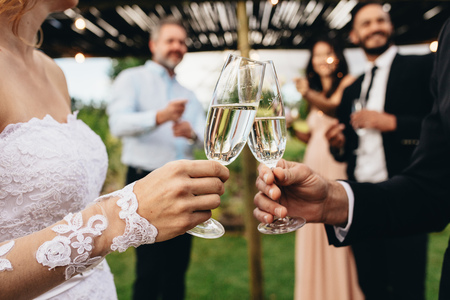 Close up of bride and groom toasting champagne glasses at wedding party. Newlyweds clinking glasses at wedding reception outside. Фото со стока
