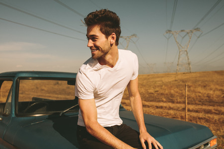 Man sitting on bonnet of a car parked during a road trip to country side. Man enjoying a road trip in country side. Stock fotó