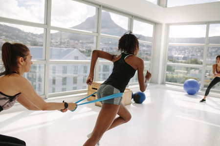 Strong woman using a resistance band in her exercise routine at fitness studio. Personal trainer and woman at gym during resistance band workout.