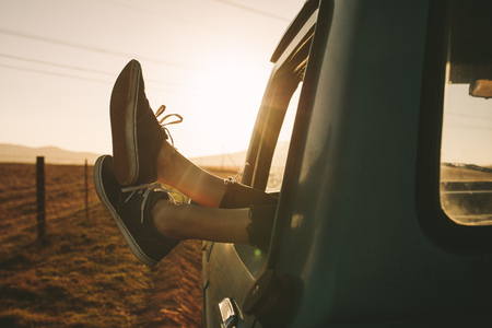 Close up of legs of a relaxing woman hanging out from car on a highway in country side. Legs hanging out from car. Фото со стока - 99749210