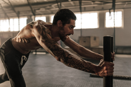Tough young man pushing sled in cross training gym. Muscular man doing intense physical training at health club. Stock Photo