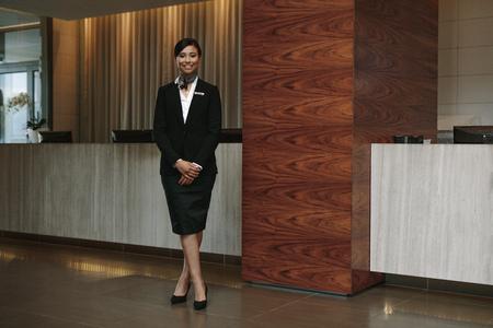 Ritratto integrale del receptionist femminile dell'hotel che sta nel luogo di lavoro. Receptionist bella donna che lavora in hotel. Archivio Fotografico