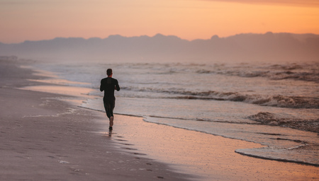 Rear view of man running on the beach in morning. Male athlete on morning run outdoors on seashore.