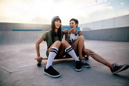 Urban girls in skate park with skateboard laughing and having fun. Two female friends sitting on a long board and laughing. Banco de Imagens