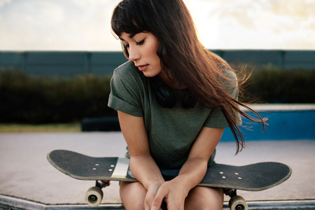 Young woman sitting at skate park with skateboard looking down. Young female skateboarded relaxing at skate park. 스톡 콘텐츠