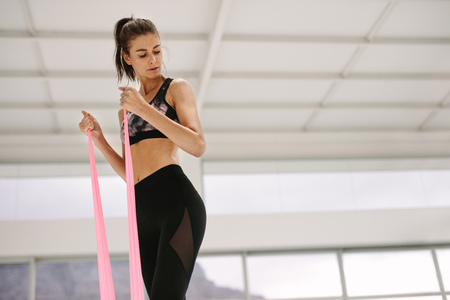 Fit woman using resistance band for arms exercise at gym. Caucasian female working out with elastic bands at fitness studio.