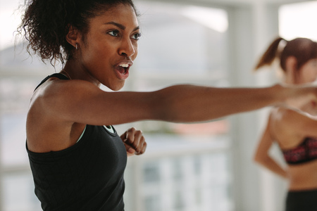 African young woman doing intense punching work out at the gym. Young slim woman in sportswear doing exercise during intensive circuit training.