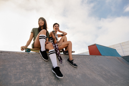 Two young urban girls in skate park laughing and having fun. Two female friends sitting on a long board. Archivio Fotografico - 99924434