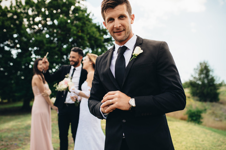 Portrait of handsome groom standing at park with his bride and friends taking selfie in background. Groom after wedding ceremony.