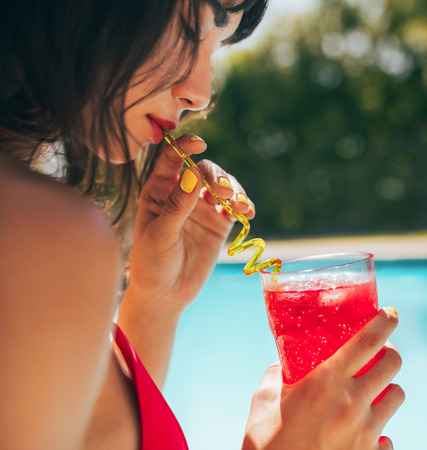 Close up of woman drinking cocktail at the poolside. Female having a drink while by the swimming pool. Reklamní fotografie