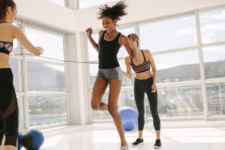 Woman jumping rope with friends rotating the rope in fitness studio. Females enjoying jumping rope workout at gym. Stok Fotoğraf
