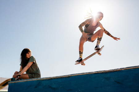 Female skater rides on skateboard with female friend sitting on ramp. Female skateboarding at skate park with friend watching the routine. Banco de Imagens