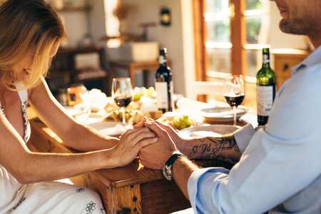 Close up of couple in love holding hands at home sitting at kitchen dining table. Close up of man and woman having romantic meal at home.