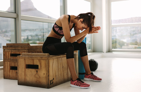 Tired looking fitness woman sitting on box at gym. Female relaxing after her intense workout at fitness studio.