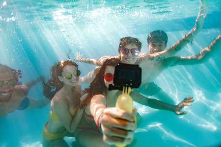 Woman taking selfie of friends with waterproof camera under the water in swimming pool. Group of young people swimming underwater and making self portrait.