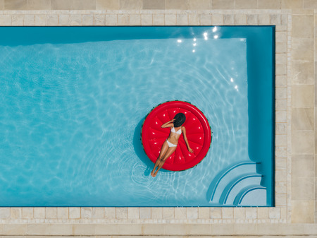 Top view of woman relaxing on a inflatable mattress in swimming pool with her face covered with hat. Female in bikini sunbathing on inflatable mattress in pool. 版權商用圖片