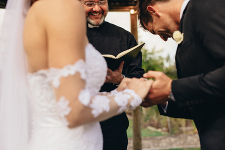 Couple holding hands with groom acknowledging the consent before the priest. Close up of bride and groom during outdoor wedding ceremony with priest questioning the consent. Banque d'images - 99924451