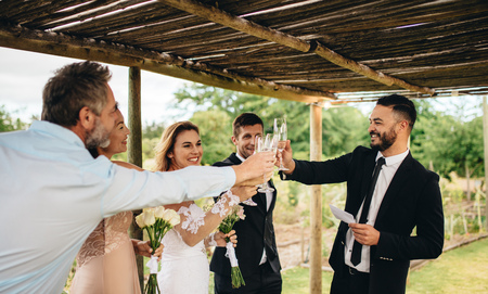 Guest toasting champagne with wedding couple. Young newlyweds clinking glasses and enjoying the moment with guest at wedding reception outside.