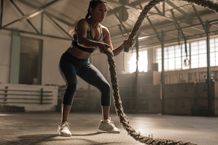 Young woman doing strength training using battle ropes at the gym. Athlete moving the ropes in wave motion as part of fat burning workout.