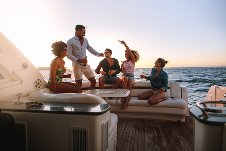 Group of happy friends having a boat party. Diverse men and women having drinks at sunset yacht party and dancing.