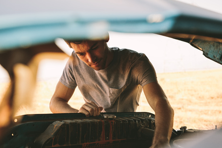 Man repairing his car opening the hood. Man fixing his car on highway on a road trip to country side. Stock Photo