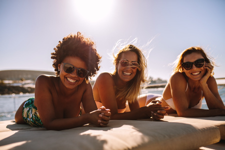Attractive females in swimsuits relaxing on a yacht deck looking at camera and smiling. Women friends sunbathing on luxury yacht and having a great time. Archivio Fotografico