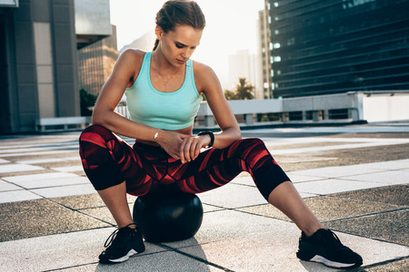 Fit young woman sitting on medicine ball checking her smartwatch. Females resting after training session and looking at her wrist watch.
