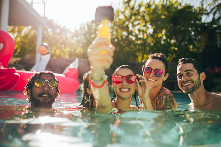 Group of happy young people enjoying summer in swimming pool and taking selfie. Friends taking selfie in the swimming pool. Stock Photo