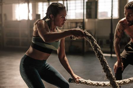 Femme exerçant avec des cordes de combat au gymnase avec entraîneur. Athlète faisant un entraînement de corde de combat au gymnase avec un entraîneur. Banque d'images