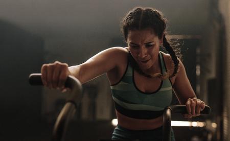 Femme de remise en forme sur vélo de gym, faire de l'exercice. Femme faisant plein d'efforts lors de l'exercice sur vélo pneumatique de gym.