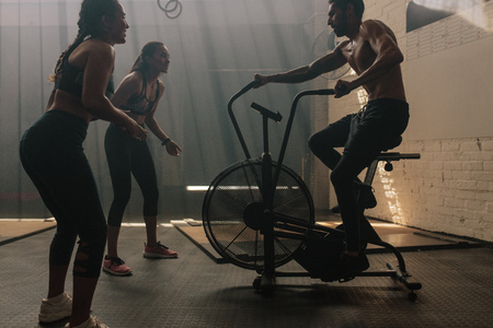 Two women motivating man exercising on air bike in gym. Man doing intense workout on gym bike with females.