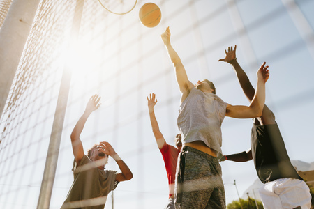 Four men playing basketball in a basketball court on a sunny day. Men jumping high to reach for the ball near the basket. Stock Photo