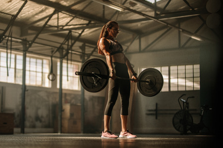 Strong female athlete holding a barbell in her hands. Cross fit woman lifting heavy weights in gym. Stok Fotoğraf