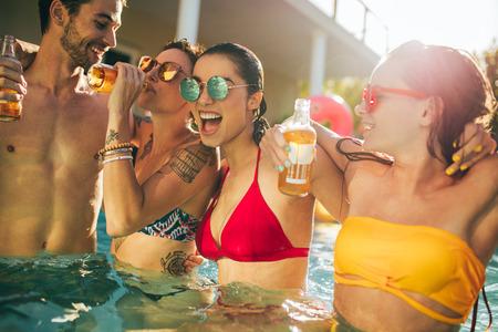 Gemischtrassige Gruppe von Freunden, die Spaß in einer Poolparty haben. Gruppe von Männern und Frauen, die zusammen im Schwimmbad trinken und genießen. Standard-Bild
