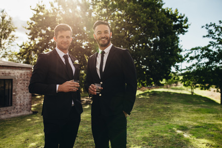 Portrait of handsome young groom standing with his friend having drinks at wedding party. Bridegroom and best men after wedding ceremony having drinks at park. Stock Photo