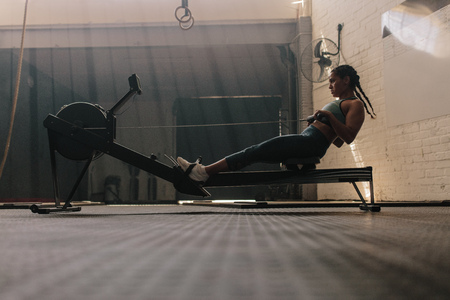 Mujer con máquina de remo en el club de salud. Mujer sana haciendo ejercicios en la máquina de fitness en el gimnasio.
