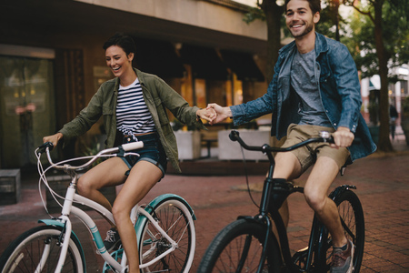 Happy young couple holding hands and riding on bikes. Smiling man and woman cycling together in the city. Reklamní fotografie