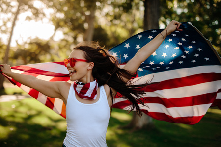 Young woman enjoying in park holding USA flag. American girl with national flag having fun at the park. 写真素材