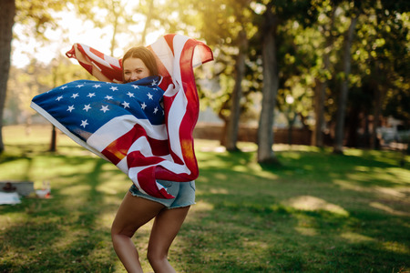 Young patriotic woman with american flag in the park looking back and smiling. Girl running with USA flag in the park.