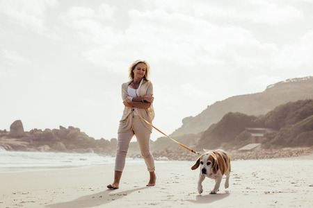 Full length shot of mature woman taking her dog on walk on the beach. Senior female on morning walk with her pet dog.