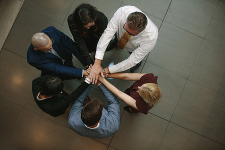 Top view of business people putting hands together. Multiracial business team stacking hands over each other. 스톡 콘텐츠