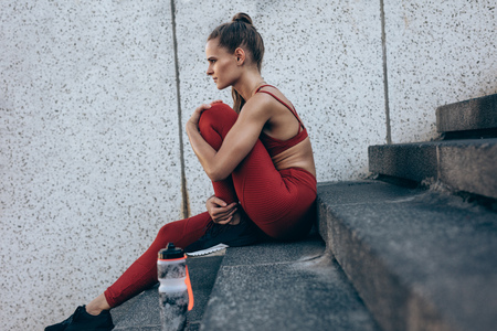 Woman in running attire sitting on steps outdoors. Fitness female resting on stairs after jogging.